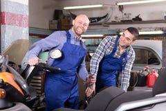 Mecânicos na estação do reparo da motocicleta Fotografia de Stock Royalty Free