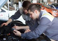Mecânicos na oficina de reparações dois mecânicos seguros que trabalham em um motor de automóveis Foto de Stock Royalty Free