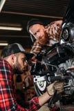 mecânicos novos consideráveis que reparam a motocicleta junto Fotografia de Stock