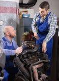 Mecânicos profissionais que reparam o carro Imagem de Stock
