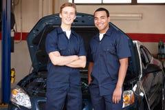Mecânicos que estão na frente do carro Fotos de Stock Royalty Free