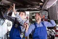 Mecânicos que fixam o carro Foto de Stock