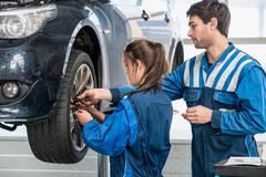 Mecânicos que mudam o pneu do carro suspendido na garagem Imagens de Stock Royalty Free