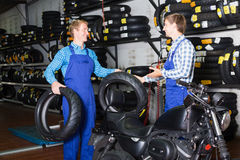Mecânicos que trabalham com pneus novos Fotografia de Stock