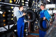 Mecânicos que trabalham com pneus novos Fotos de Stock Royalty Free