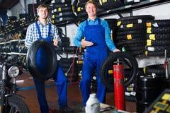 Mecânicos que trabalham com pneus novos Foto de Stock