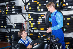 Mecânicos que trabalham com pneus novos Imagem de Stock