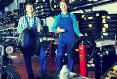 Mecânicos que trabalham com pneus novos Imagem de Stock Royalty Free