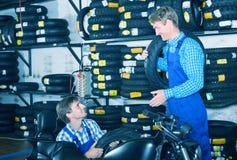 Mecânicos que trabalham com pneus novos Fotos de Stock