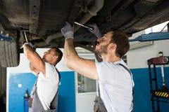 Mecânicos que trabalham sob o carro Fotos de Stock