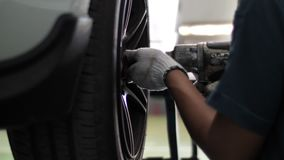 Mec?nico de autom?viles que trabaja en frenos en un garaje nacional del taller de reparaciones del coche almacen de metraje de vídeo