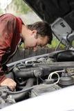 Mecanicista joven controlando un motor de coche Fotografía de archivo