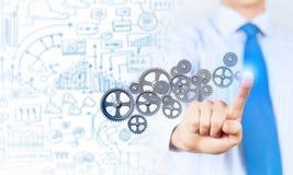 Mecanismo de engranajes del hombre de negocios que activa Imagen de archivo