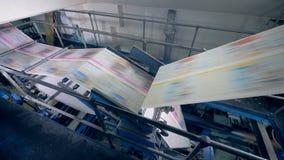 Mecanismo de la fábrica y periódico impreso que ruedan rápidamente a través de él almacen de video