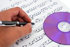 Mecanismo impulsor del Cd o del dvd y notas musicales Foto de archivo libre de regalías