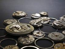 Mecanismos de relojes y de sus partes en un fondo negro imagenes de archivo