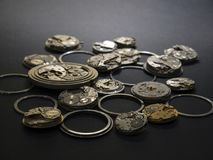 Mecanismos de relojes y de sus partes en un fondo negro imagen de archivo