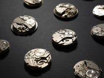 Mecanismos de relojes y de sus partes en un fondo negro foto de archivo libre de regalías