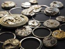 Mecanismos dos relógios e das suas partes em um fundo preto foto de stock
