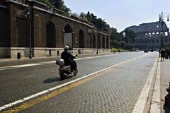 Mecanismos impulsores de la vespa hacia el colloseum en Roma imágenes de archivo libres de regalías