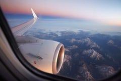 Mecanografíe adentro la ventana del avión de las montañas foto de archivo libre de regalías
