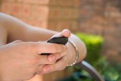 Mecanografiar un mensaje en un teléfono móvil Fotografía de archivo