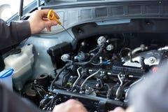 Meccanici all'officina riparazioni due meccanici che lavorano ad un motore di automobile Fotografia Stock