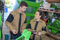 Meccanici del gruppo due che lavorano nella tettoia dell'azienda agricola Fotografie Stock
