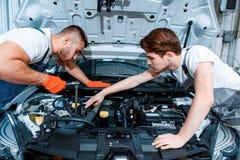 Meccanici di automobile al distributore di benzina fotografia stock libera da diritti