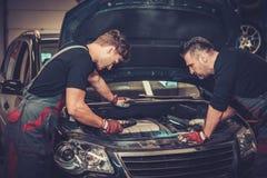 Meccanici di automobile che controllano sotto il cappuccio nel servizio di riparazione automatica fotografie stock libere da diritti
