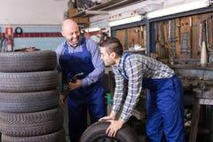 Meccanici di automobile che lavorano al carshop Immagine Stock