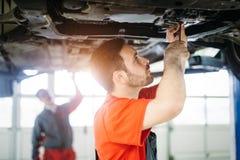 Meccanici di automobile che lavorano al centro di servizio automobilistico immagine stock libera da diritti