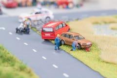 Meccanici miniatura che sostituiscono un pneumatico fuori dalla carreggiata Immagini Stock Libere da Diritti