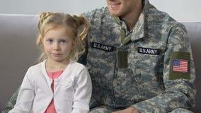 Meccanico americano che abbraccia la bandiera nazionale sveglia della tenuta della figlia, patriottismo archivi video