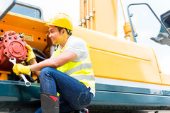 Meccanico asiatico che ripara il veicolo della costruzione Fotografia Stock