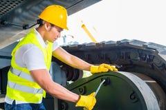 Meccanico asiatico che ripara il veicolo della costruzione Immagini Stock