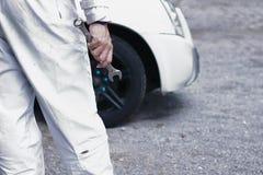 Meccanico automobilistico in chiave della tenuta dell'uniforme di bianco in sue mani pronte a riparare il motore di automobile Co fotografie stock