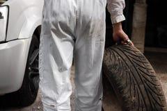Meccanico automobilistico in uniforme con la gomma e la chiave per l'automobile di riparazione ai precedenti del garage di ripara immagine stock