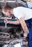 Meccanico bello con l'automobile della riparazione della chiave Fotografie Stock