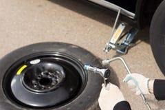 Meccanico che cambia un pneumatico dell'automobile Immagini Stock Libere da Diritti