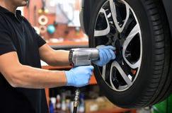 Meccanico che cambia una gomma di automobile in un'officina Immagini Stock