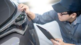 Meccanico che controlla il faro dell'automobile facendo uso della compressa fotografie stock