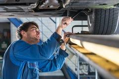 Meccanico che esamina la sospensione di un'automobile durante la prova di MOT fotografia stock