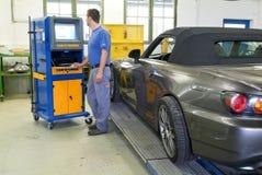 Meccanico che fa l'allineamento di ruota sul suo garage Immagini Stock
