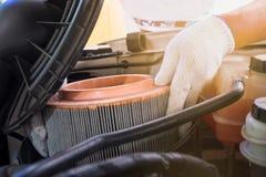 meccanico che indossa i guanti protettivi del lavoro che tengono uno sporco Immagine Stock