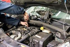 Meccanico che lavora ad un motore di automobile che fa le riparazioni immagine stock