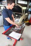Meccanico che lavora al computer portatile Fotografia Stock