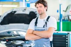 Meccanico che lavora nell'officina dell'automobile fotografia stock libera da diritti