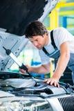 Meccanico che lavora nell'officina di servizio dell'automobile immagine stock libera da diritti