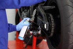 Meccanico che lubrifica una catena del motociclo Fotografia Stock Libera da Diritti